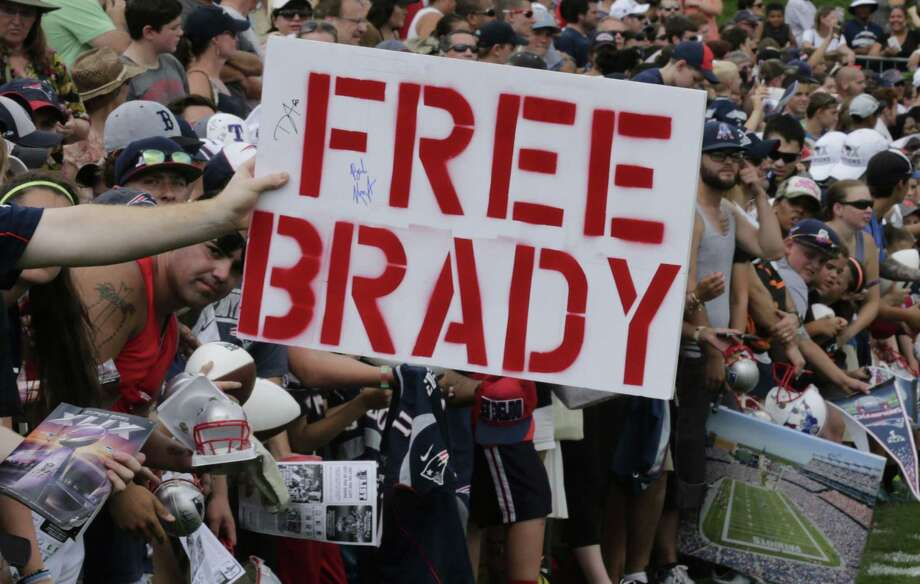 """A New England Patriots fan holds a """"Free Brady"""" sign during an NFL football training camp in Foxborough, Mass., Thursday, July 30, 2015. (AP Photo/Charles Krupa) Photo: AP / AP"""