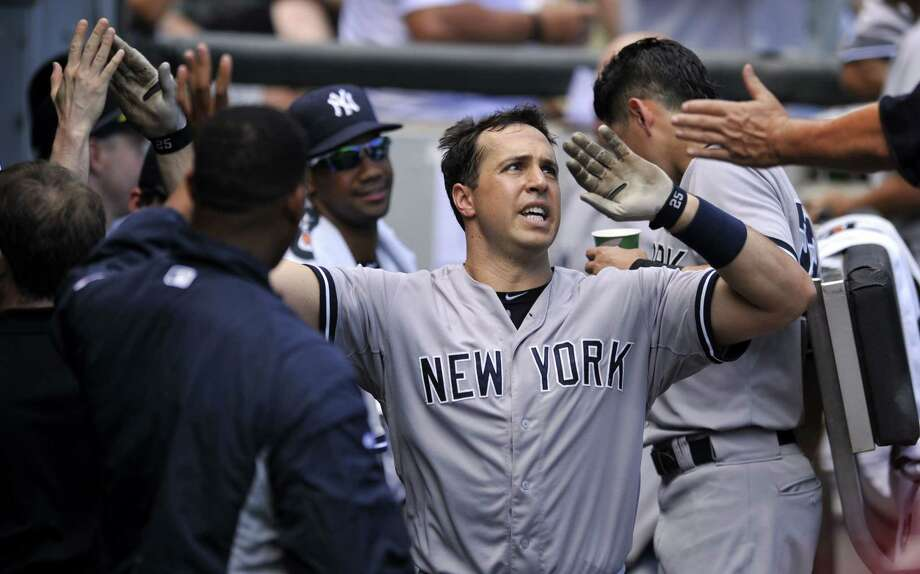 The Yankees' Mark Teixeria celebrates with teammates in the dugout after hitting a solo home run in the fifth inning Sunday. Photo: Paul Beaty — The Associated Press   / FR36811 AP