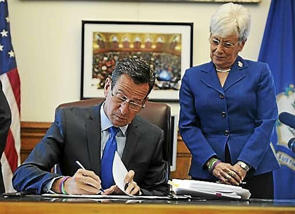 Connecticut Gov. Dannel P. Malloy signs the budget in his office as Lt. Gov. Nancy Wyman, right, looks on, at the state Capitol on June 30, 2015 in Hartford.