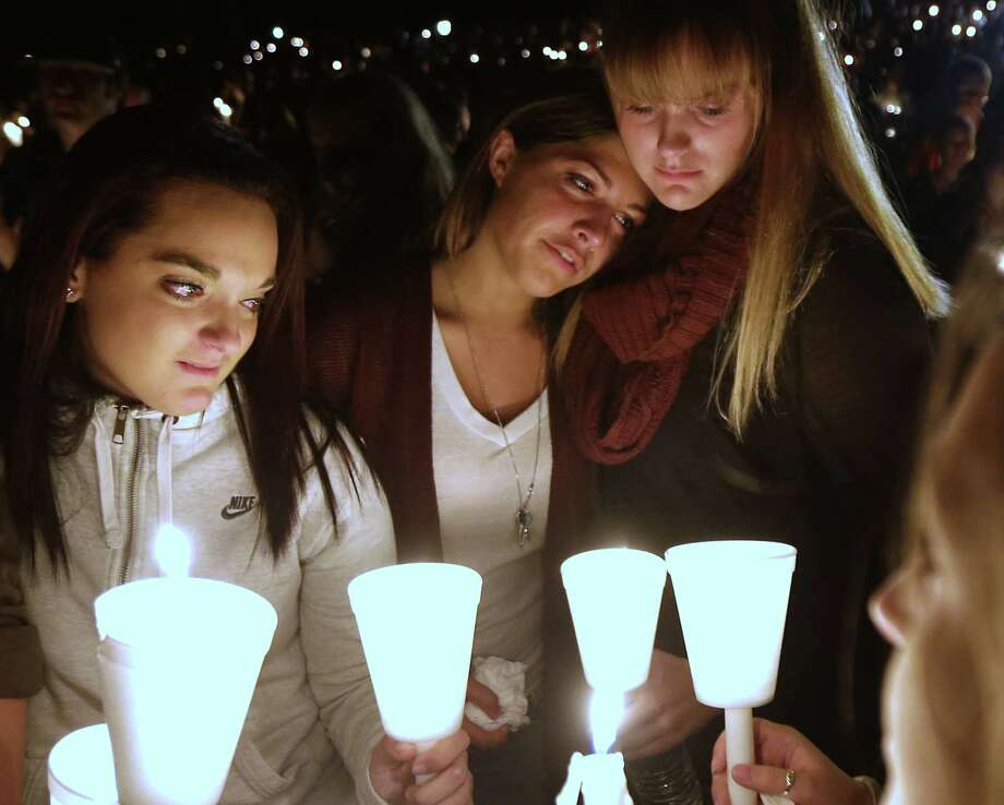 Umpqua Community College students Nicole Zamarripa, left, Kristen Sterner, center and Carrissa Welding, right, join others at Stewart Park, in Roseburg, Ore., for a candlelight vigil for those killed during a fatal shooting at the school Thursday, Oct. 1, 2015. (AP Photo/ Photo: Rich Pedroncelli — The Associated Press   / AP