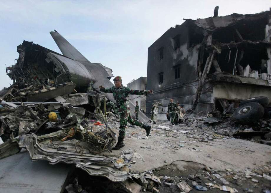 Rescuers search for victims at the site where an Indonesian air force transport plane crashed in Medan, North Sumatra, Indonesia, Wednesday, July 1, 2015. The C-130 Hercules plane crashed into a residential neighborhood in the country's third-largest city on June 30. (AP Photo/Binsar Bakkara) Photo: AP / AP