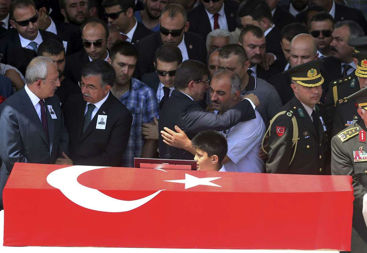 Turkey's Prime Minister Ahmet Davutoglu, centre, embraces the father, name not available, of late Turkish soldier Hamza Yildirim, next to his Turkish flag-draped coffin during the funeral ceremony at Kocatepe Mosque in Ankara, Turkey on July 31, 2015. Yildirim was one of the three Turkish troops that were killed on July 30 when Kurdistan Workers' Party, or PKK militants opened fire on their convoy in the southeastern province of Sirnak, according to the army.