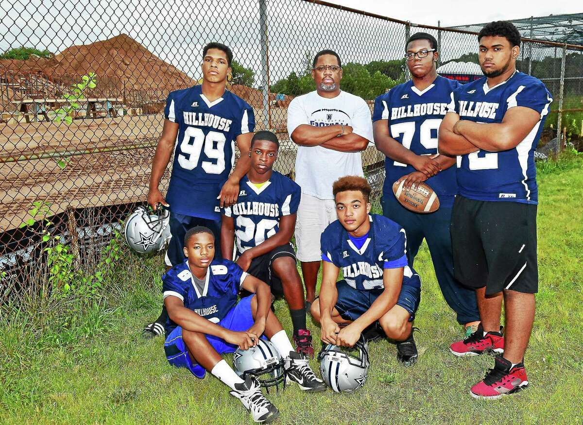 Members of the James Hillhose High School football team, junior Damian Henderson (8), seated at left, sophomore Corey Pollard (20), kneeling, sophomore JT Gardner (13), senior AndrÈ Wooten (99), Head coach Reggie Lytle, senior Noah Brown (79) and senior Fredrick Singh (72) are concerned by the mounds of dirt at Bowen Field and question the district's promise that the field will be completed for the team to play the Elm City Classic in November. (Catherine Avalone - New Haven Register)