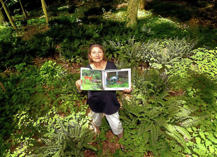 Patricia Kelly holds a book of her photographs she made and opened to a page depicting rare Piebold Deer, and other flaura, fauna, insects and reptiles that inhabit a Wheeler's Farms Road area in Milford as proof to the Planning and Zoning Board of Milford that a proposed multi-family, affordable housing complex near the road will hurt the habitat there. She has lived on  Wheeler's Farms Road for 40 years and the family homestead has been there since the 1920s. Photo: Peter Hvizdak — New Haven Register   / ©2015 Peter Hvizdak
