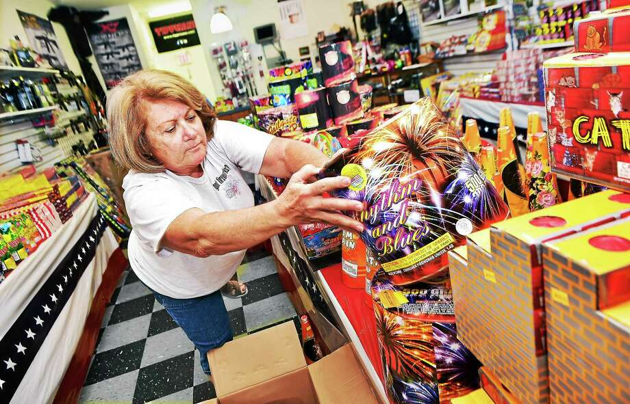 """Joann Spillane, owner of Uncle Guido's Fireworks & Xtreme Paintball at 71 W. Main St. in Branford, stocks the shelves Wednesday. Spillane began selling fireworks in 2000 with her husband, Dan """"Uncle Guido"""" Spillane, now deceased. """"This is my favorite time of year,"""" Spillane said. Photo: Catherine Avalone — New Haven Register    / New Haven RegisterThe Middletown Press"""