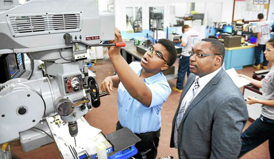 Platt Technical High School sophomore Alex Crawford, center, 14, demonstrates a milling machine for Paul Broadie, president of Housatonic Community College, at the Milford school Thursday. Photo: Arnold Gold — New Haven Register