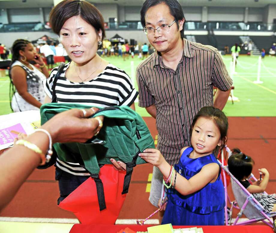Freya Xiong (bottom right), 6, of New Haven receives a new backpack during the annual Back-to-School Rally at the Floyd Little Athletic Center in New Haven on 8/1/2015.  She is with her mother, Kai Li, father, Hai Xiong, and sister, Cynthia Xiong. Photo: Arnold Gold-New Haven Register