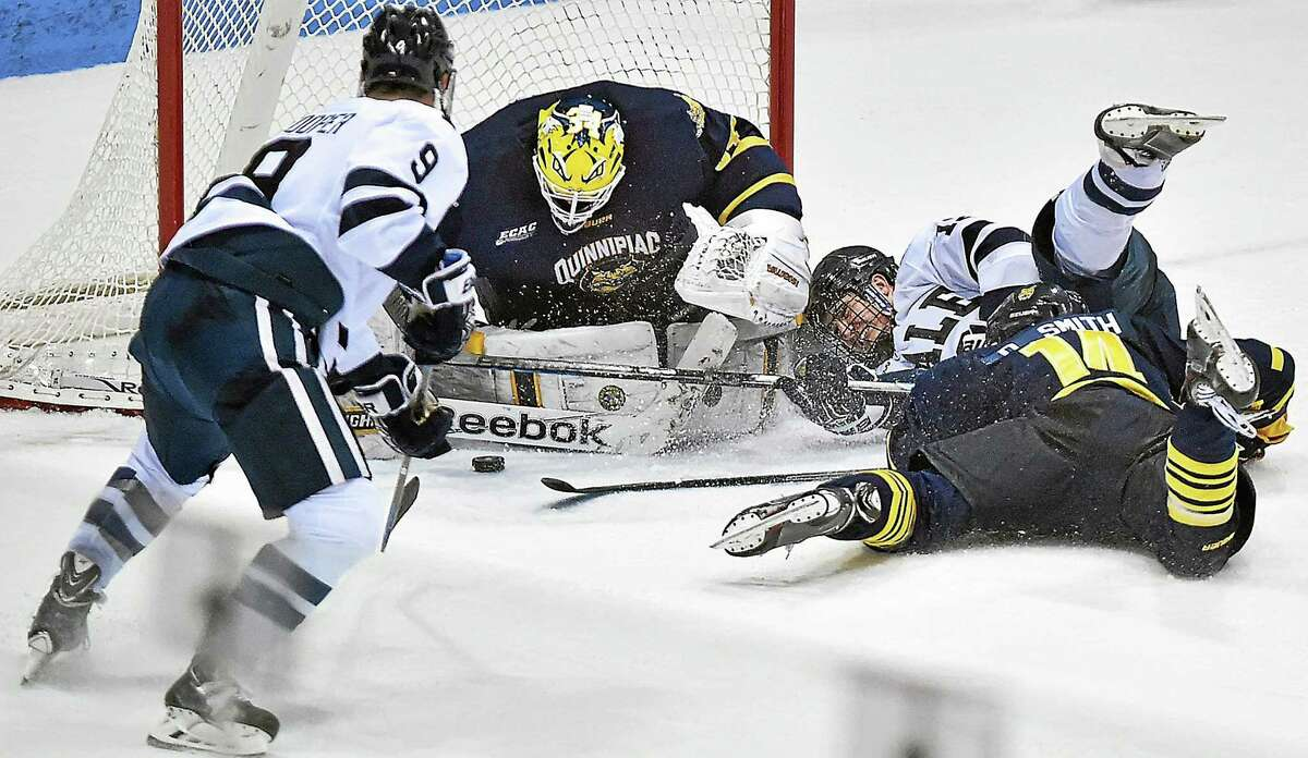 Yale's Cody Learned (12) and Carson Cooper (9) battle at the Quinnipiac net with goalie Michael Garteig and Derek Smith (14) during a 2-2 tie on Saturday night at Ingalls Rink.