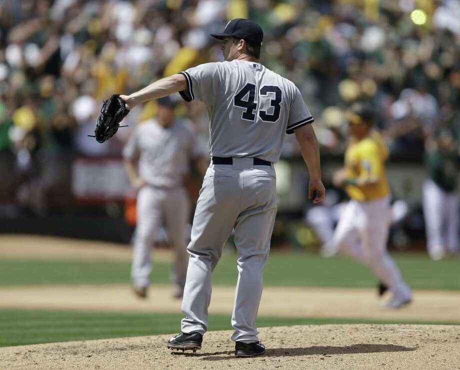 The Yankees' Adam Warren (43) waits for a new ball as the Athletics' Stephen Vogt runs the bases after hitting a two-run home run. Photo: Ben Margot — The Associated Press   / AP
