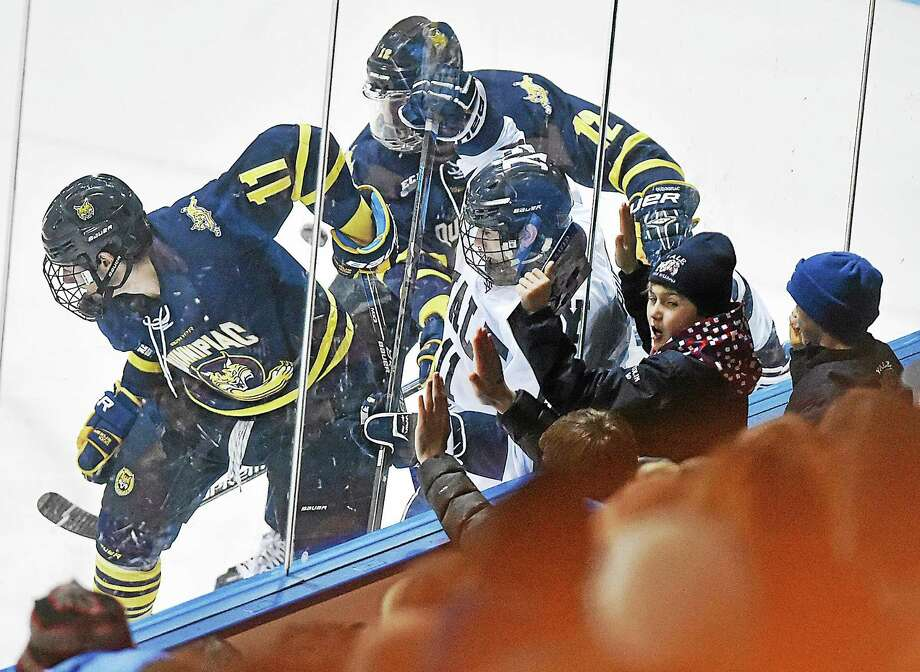 Three young hockey fans pound on the glass as Quinnipiac's Tim Clifton (11) and Justin Agosta (12) battle Yale's Trent Ruffolo (11) during a 2-2 tie on Saturday night at Ingalls Rink. Photo: Catherine Avalone — Register   / Catherine Avalone/New Haven Register