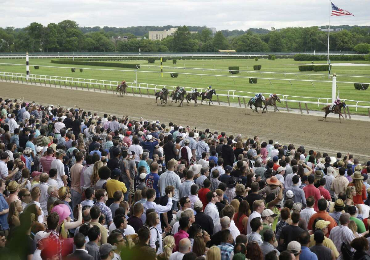 In this June 8, 2013 photo, fans cheer race horses as they near the finish line at Belmont Park in Elmont, N.Y.