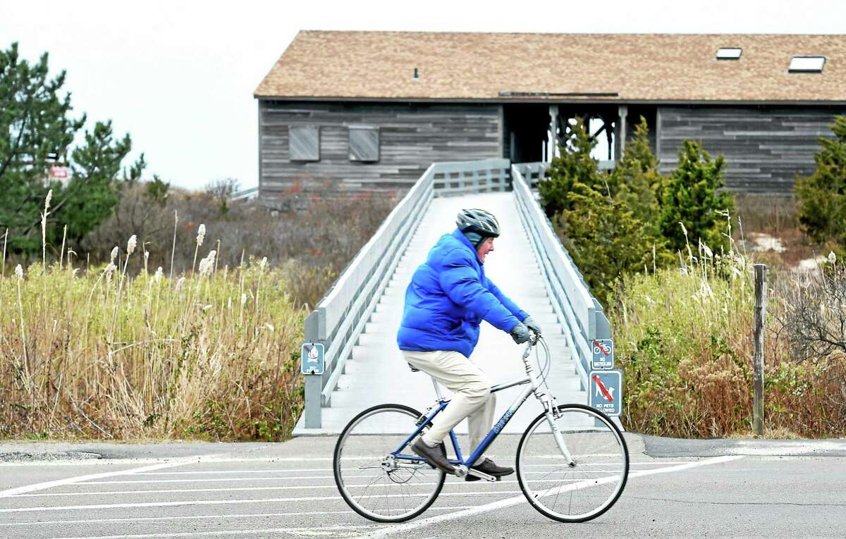 (Arnold Gold-New Haven Register) Bundled up for the cold weather, Gerald Cammack of Madison rides past Meigs Point at Hammonasset Beach State Park in Madison on 12/8/2014.