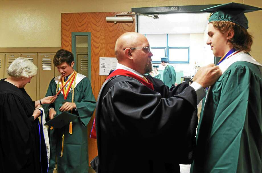 Valedictorian Andrew George Jefferies of Hamden, second from left, with Margaret Sanders, Chairman of the Notre Dame H.S. Math Department, left, and Michael Abbott, Chair of Notre Dame H.S. Math Department and Senior Class Moderator, third from left, straightening out honor medals on the graduation gown of Salutatorian Cameron J. Hines of Ansonia before the start of the Notre Dame High School 66th Annual Commencement Exercises in West Haven, Connecticut, on Sunday, May 31, 2015. Jefferies and Hines were Math Club members. Photo: Peter Hvizdak--New Haven Register   / ©2015 Peter Hvizdak