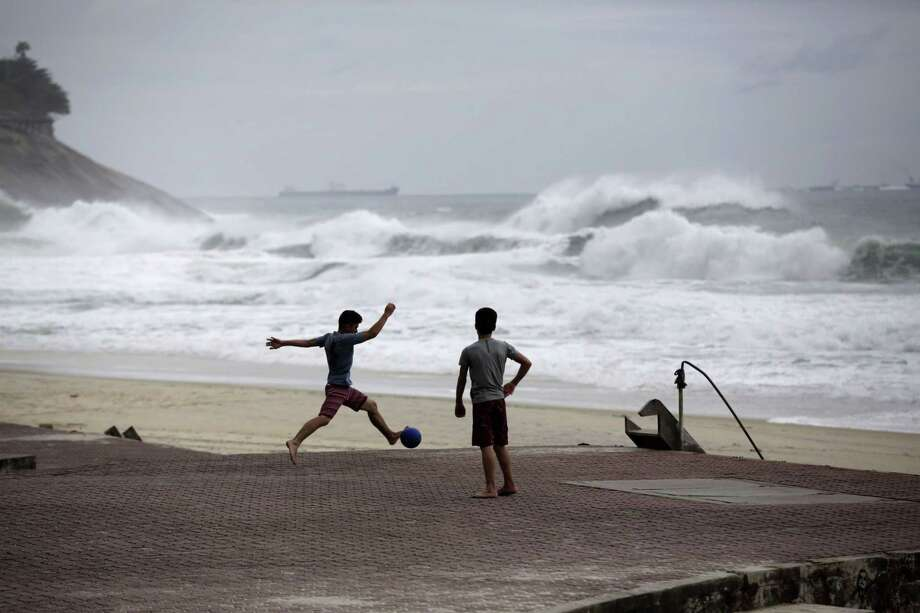 FILE - In this June 20, 2014 file photo, boys play football as waves break on Sao Conrado beach in Rio de Janeiro, Brazil. World Surf League spokesman Dave Prodan said in an emailed statement Wednesday, April 29, 2015, that Sao Conrado beach had to be removed from its venue list ìdue to pollution issues.î The beach had been a backup for the May 11-22 Rio Pro event, to be used in case of sub-par waves or other issues at the primary venue, nearby Barra da Tijuca beach. (AP Photo/Matt Dunham, File) Photo: AP / AP