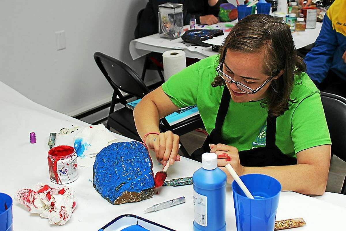 Lizzie puts finishing touch on her work at Vista Vocational Life Skills Center.