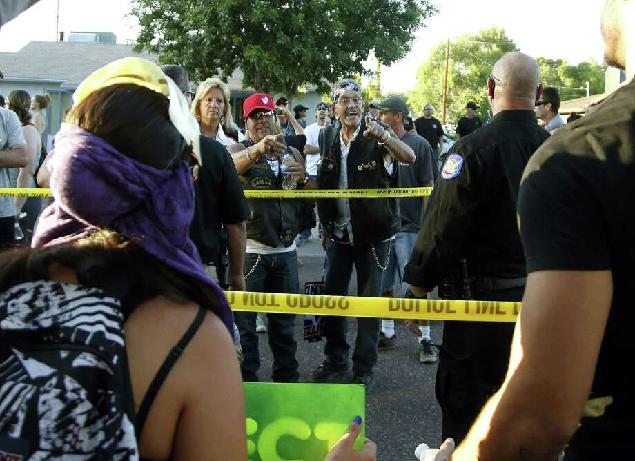 Protesters gather outside the Islamic Community Center of Phoenix, Friday, May 29, 2015. About 500 protesters gathered outside the Phoenix mosque on Friday as police kept two groups sparring about Islam far apart from each other. (AP Photo/Rick Scuteri) Photo: AP / 157181 AP