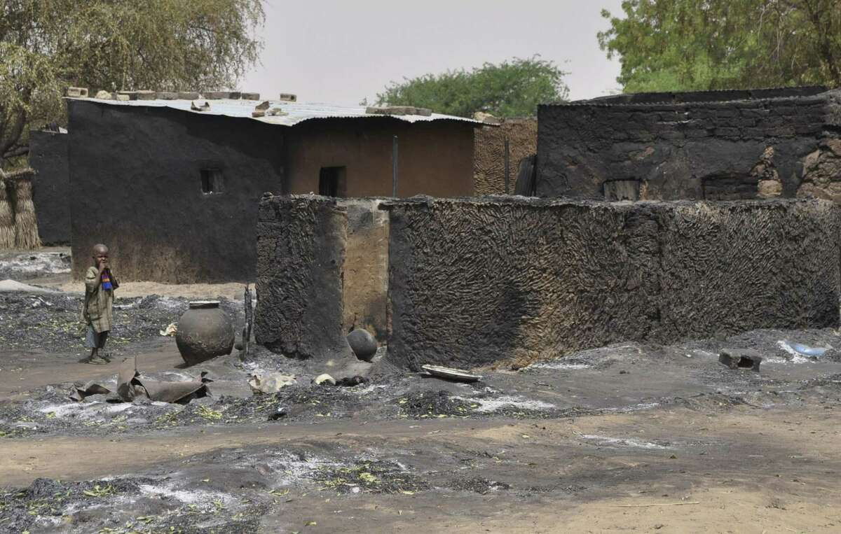 A child walks past burnt out houses following Sunday's attack by Boko Haram militants in Gubio, Nigeria, Tuesday, May 26, 2015. Children are now being seen as potential threats after an