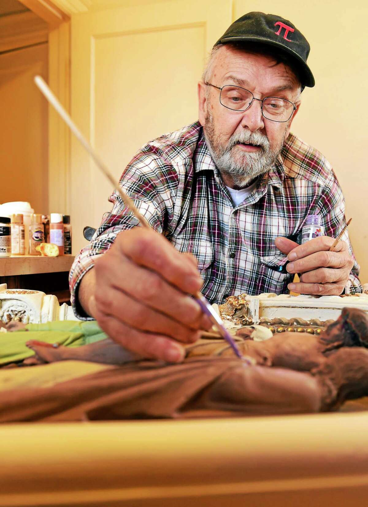 Edwin Norse, owner of Saint Joseph's Statue Repair of Middletown, 68, demonstrates his patient brush strokes on a restoration of a Station of the Cross at the St. Ann Roman Catholic Church on Dixwell Ave. in Hamden, Tuesday, March 31, 2015. He pushes through his own pain to restore life to objects that are dying. Methodically, with bent and painful fingers, he restores and renews the plaster and concrete Stations of the Cross and statues.