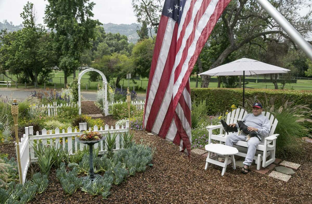 Retiree Raymond Aleman sits with his Chihuahua dogs, Justin and Jason, at his drought resistant garden in the Studio City neighborhood in Los Angeles.