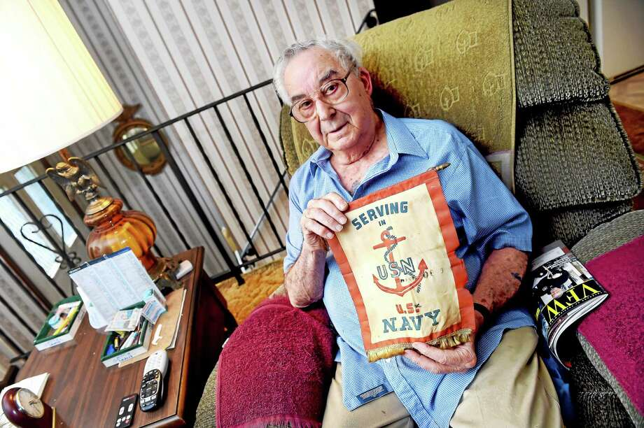 World War II Navy veteran Joseph Maturo Sr., at his home in East Haven, holds a banner that hung in the window of his family's home while he served during wartime. Photo: Arnold Gold — New Haven Register