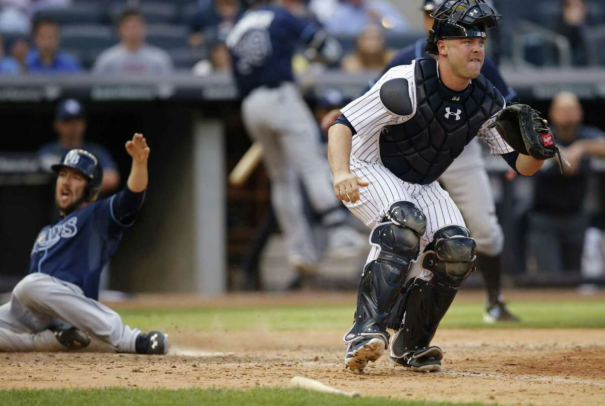 Yankees catcher Brian McCann, right, waits for the throw as Tampa Bay Rays outfielder Steven Souza Jr. scores on James Loney's 13th-inning, RBI single on Wednesday in New York.