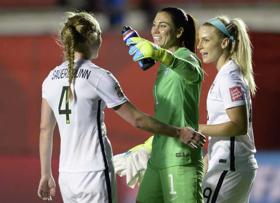 U.S. goalie Hope Solo and teammates Julie Johnston (19) and Becky Sauerbrunn (4) celebrate the team's win over China on Friday. Photo: Adrian Wyld — The Associated Press   / The Canadian Press