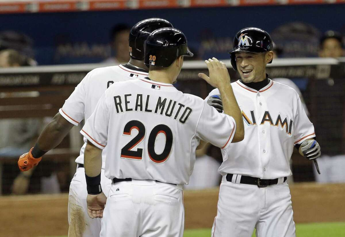 Miami Marlins left fielder Ichiro Suzuki, right, is congratulated after batting a three-run home run, by teammates Jacob Realmuto (20) and Marcell Ozuna in the eighth inning of a baseball game against the New York Mets, Wednesday, April 29, 2015, in Miami. The Marlins won 7-3. (AP Photo/Alan Diaz)