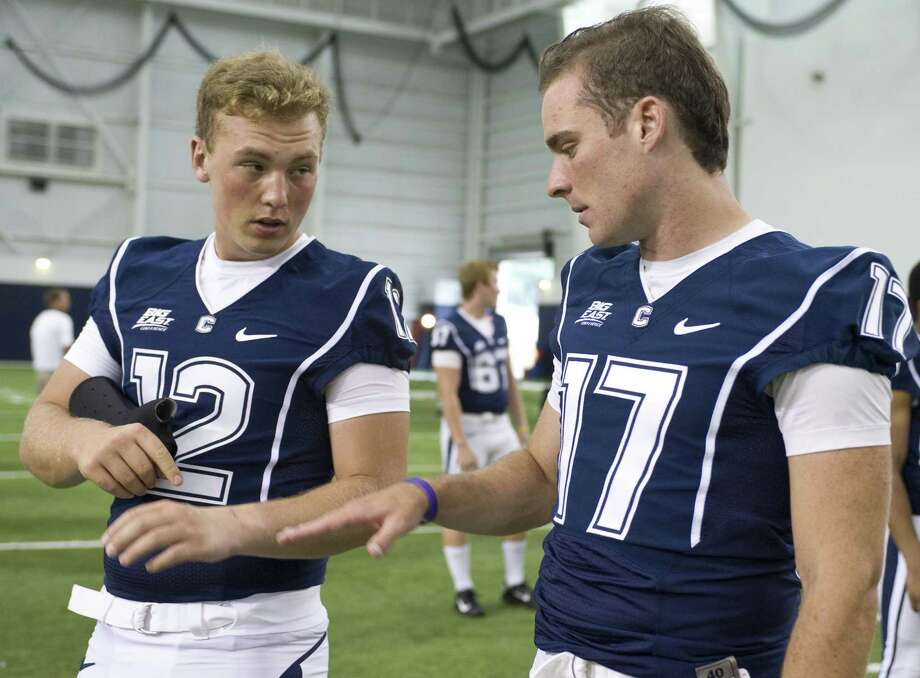 Former UConn quarterback Casey Cochran, left, takes a brace off to show his injury to fellow quarterback Blaise Driscoll, right, during an NCAA football media day in Storrs, Conn. on Aug. 10, 2012. Photo: AP Photo/Jessica Hill   / FR125654 AP