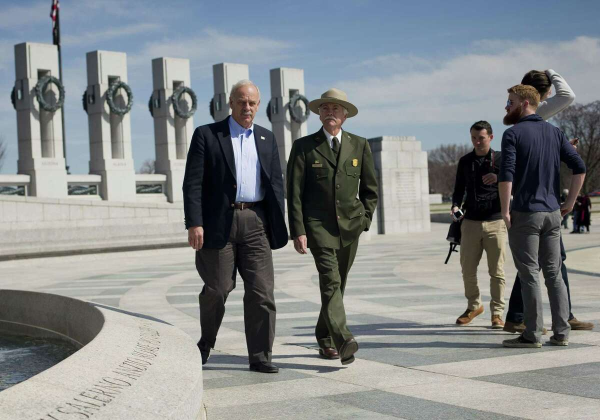 In this March 23, 2015 photo, National Park Service Director Jonathan B. Jarvis, second left, and the head of the National Park Foundation Dan Wenk, left, walk at the World War II Memorial on the National Mall in Washington.