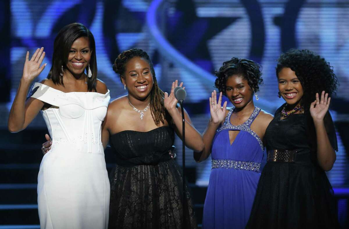 First Lady Michelle Obama, left, waves while standing on stage with Making A Difference award winners, from left, Kaya Thomas, Chental-Song Bembry and Gabrielle Jordan during a taping of the Black Girls Rock award ceremony at the New Jersey Performing Arts Center on March 28, 2015, in Newark.