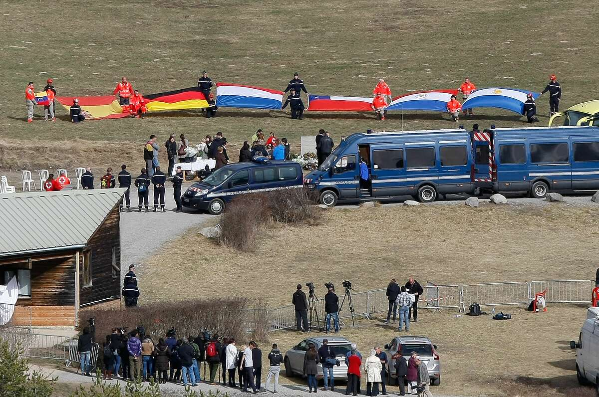 Flags representing differents nations are deployed during ceremony with family members of victims in front of a stele, a stone slab erected as a monument, set up in memory of the victims in the area where the Germanwings jetliner crashed in the French Alps, in Le Vernet, France, Sunday.
