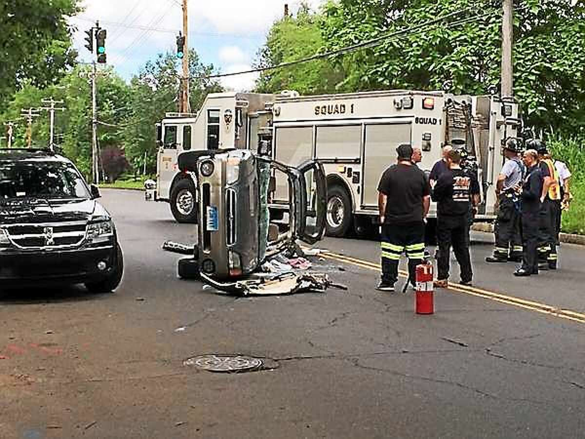 Emergency responders work to clear a rollover crash Monday morning near the Bella Vista apartments on Eastern Street in New Haven. One person was hurt in the accident.