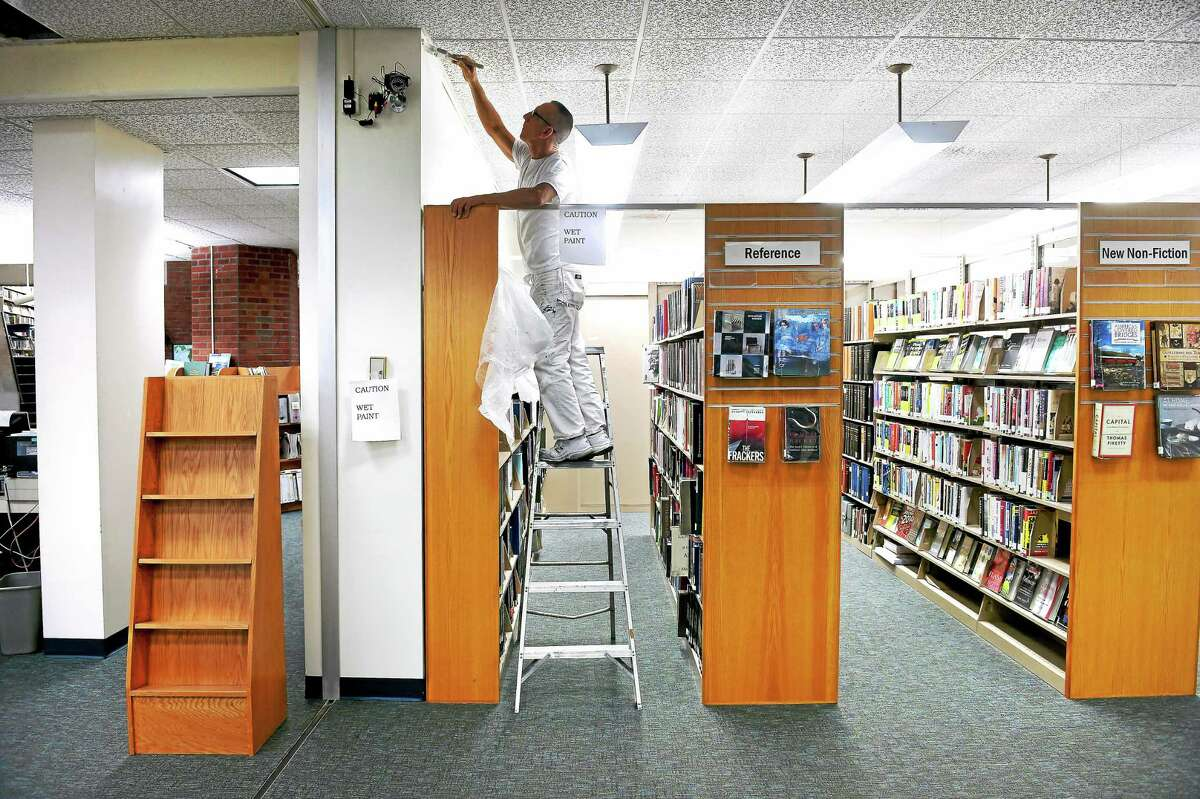 (Arnold Gold-New Haven Register) Paul Tirella of Peter Webster Painters paints in the reference area of the Miller Memorial Library in Hamden on 12/18/2014.