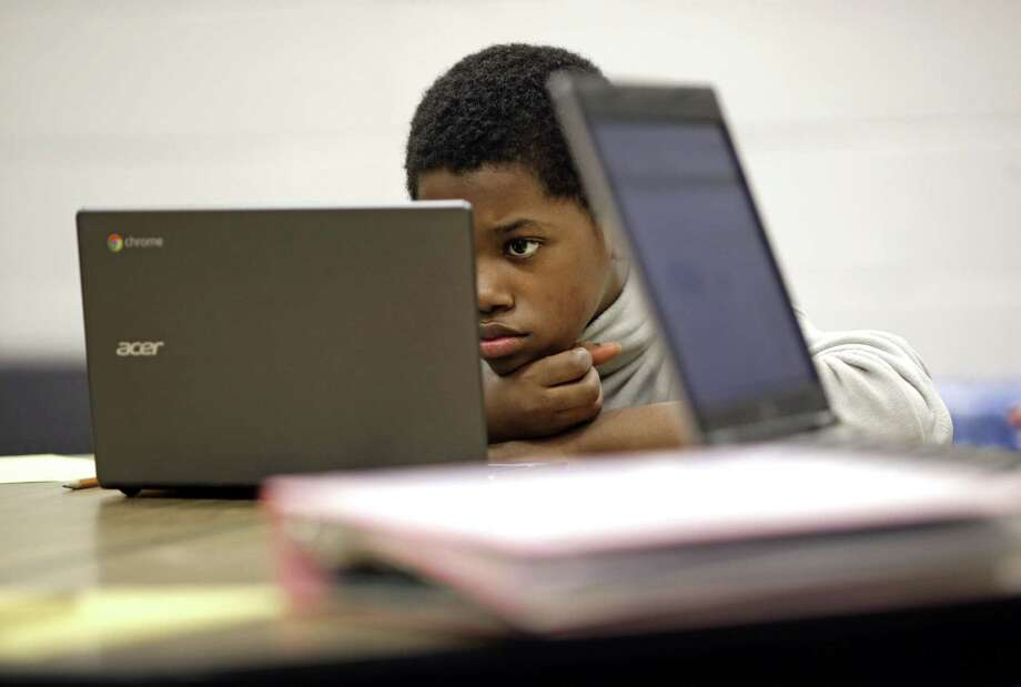 Marquez Allen, 12, reads test questions on a laptop computer during in a trial run of a new state assessment test at Annapolis Middle School in Annapolis, Md. The new test, which is scheduled to go into use Monday, is linked to the Common Core standards, which Maryland adopted in 2010 under the federal No Child Left Behind law. Photo: Patrick Semansky — The Associated Press   / AP