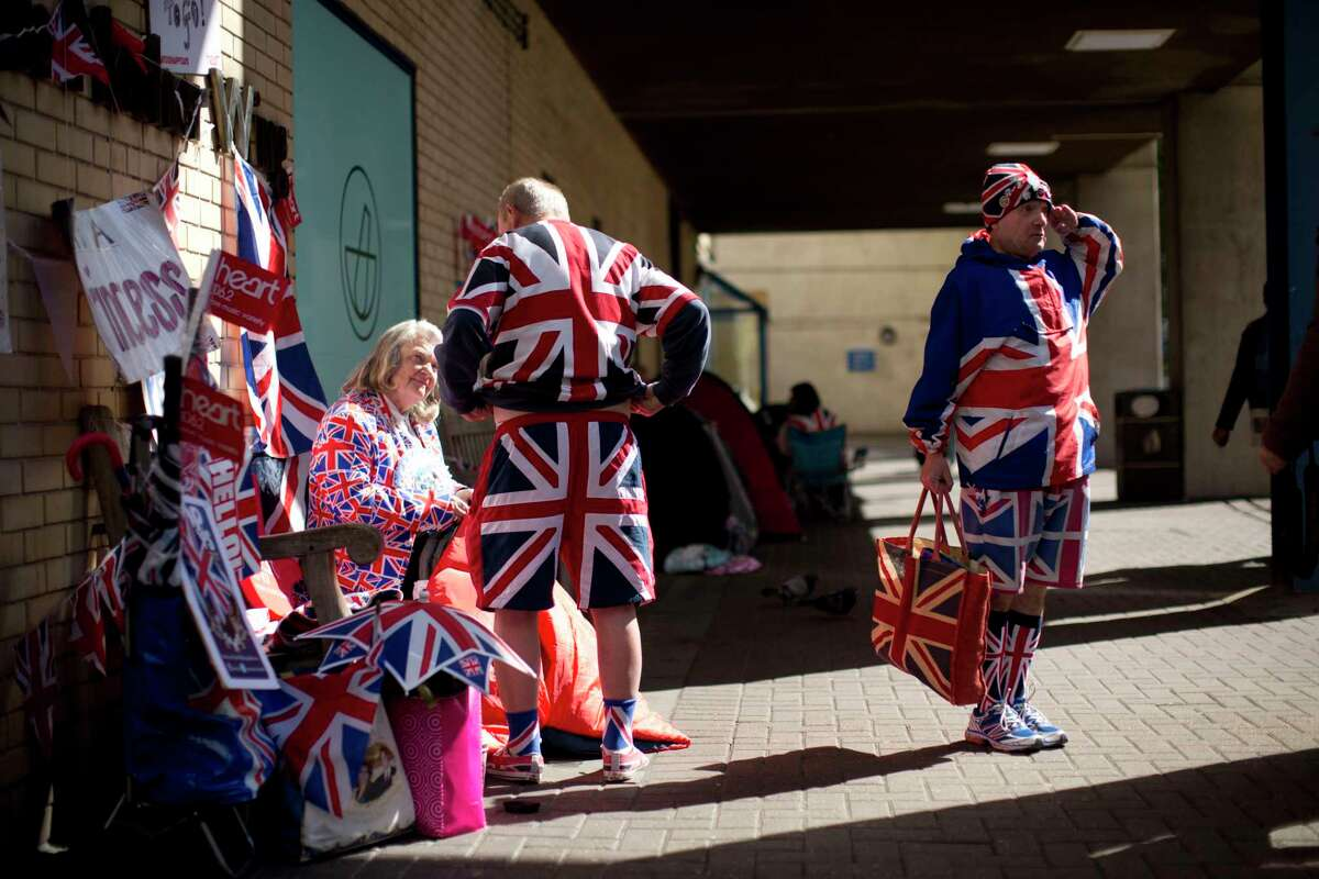 In their Union flag outfits royal fans John Loughrey, right, aged 60 stood posing in reaction to media cameras pointing in his direction, Margaret Tyler, aged 71, and Terry Hutt, aged 80, wait across the street from the Lindo Wing of St. Mary's Hospital in London, Monday, April 27, 2015. Britain's Kate the Duchess of Cambridge is expected to give birth to her second child with her husband Prince William at the hospital in the coming days. Palace officials have said the baby is due in late April. A small number of dedicated royal fans are waiting or camping outside the hospital awaiting the imminent birth. (AP Photo/Matt Dunham)