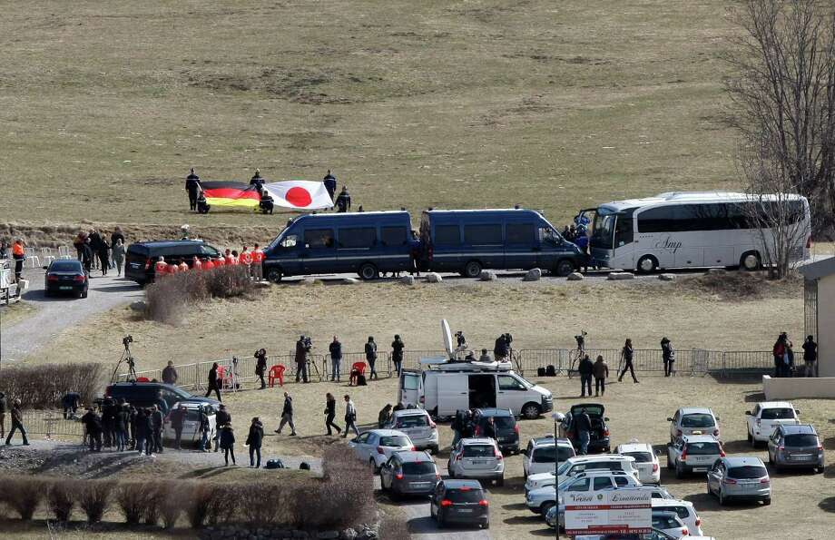 The German, left, and Japanese flags are deployed during an homage ceremony with  family  members of Japanese victims in the area where the Germanwings jetliner crashed in the French Alps, in Le Vernet, France, on March 29, 2015. The crash of Germanwings Flight 9525 into an Alpine mountain Tuesday killed all 150 people aboard. Photo: AP Photo/Claude Paris   / AP
