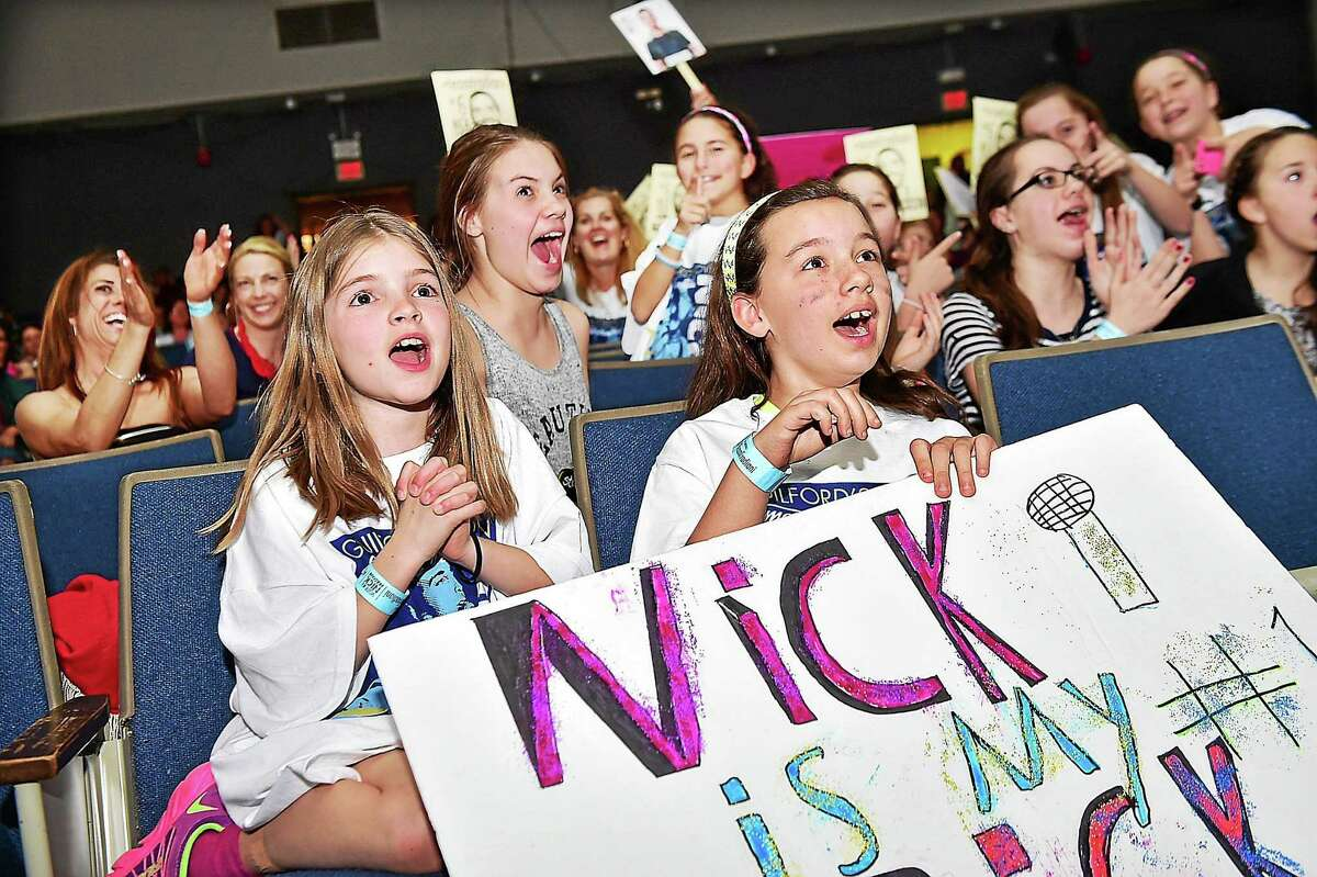Guilford residents Tania Evans, 9, left, Emma Meglin, 10, back center, and Elizabeth Barcello, 9, right, cheer for Nick Fradiani at the American Idol Viewing Party Wednesday at Guilford High School.