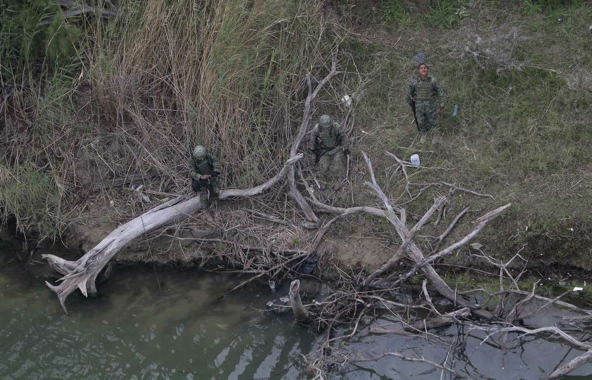 In this Feb. 24, 2015 photo, Mexican officials examine a body, lower center in the water, discovered by the U.S. Customs and Border Protection Air and Marine while on patrol near the Texas-Mexico border, in Rio Grande City, Texas.