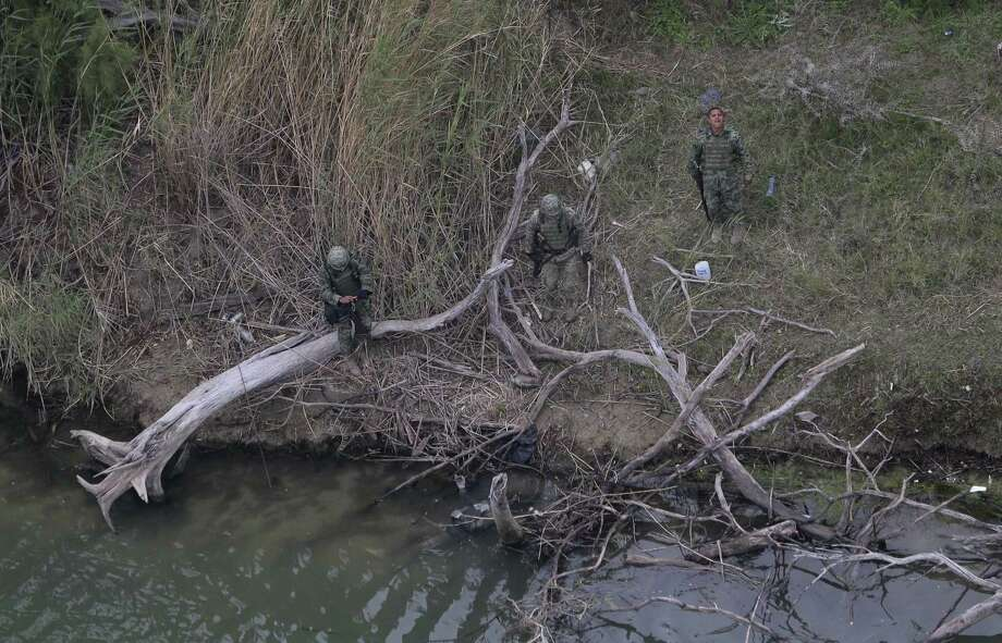 In this Feb. 24, 2015 photo, Mexican officials examine a body, lower center in the water, discovered by the U.S. Customs and Border Protection Air and Marine while on patrol near the Texas-Mexico border, in Rio Grande City, Texas. Photo: AP Photo/Eric Gay   / AP