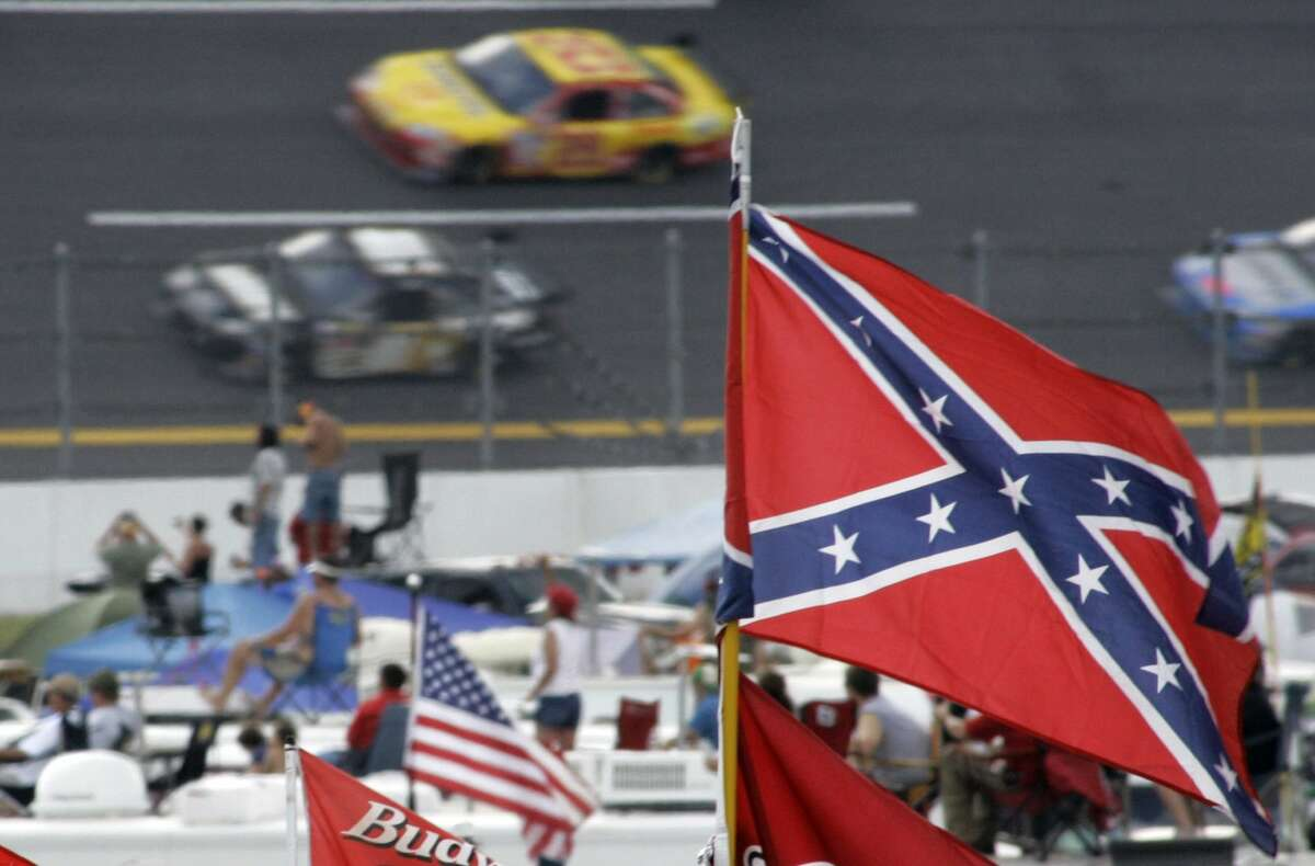 In this Oct. 7, 2007 photo, Confederate flags fly in the infield as cars come out of turn one during a NASCAR auto race at Talladega Superspeedway in Talladega, Ala. NASCAR is backing South Carolina Gov. Nikki Haley's call to remove the Confederate flag from the South Carolina Statehouse grounds in the wake of a massacre at a Charleston church, it said in a statement Tuesday, June 23, 2015.