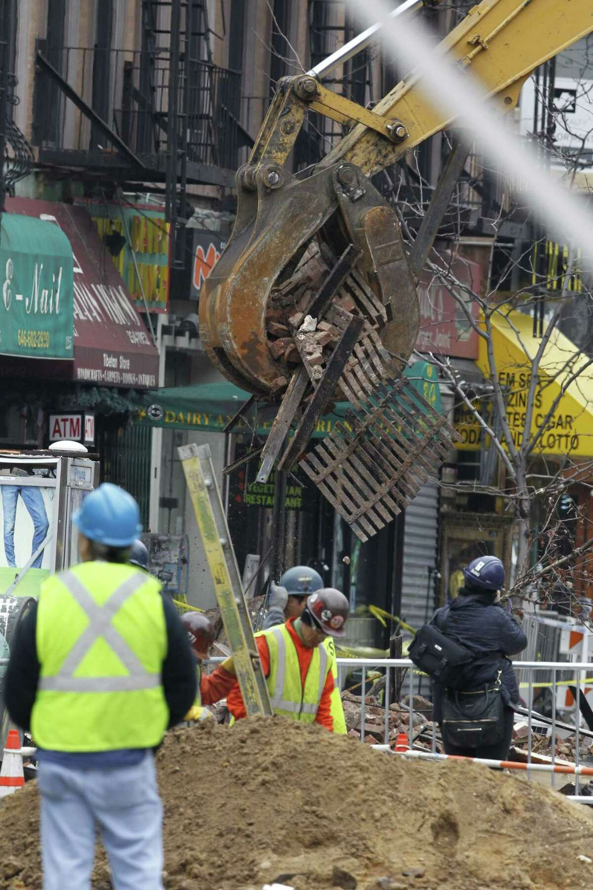 Debris are cleaned up from the site of a building collapse in the East Village neighborhood of New York on March 27, 2015. Nineteen people were injured, four critically, after the powerful blast and fire sent flames soaring and debris flying Thursday afternoon.