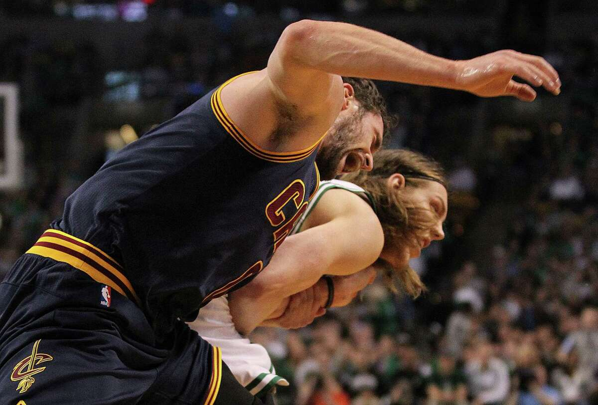 Cleveland Cavaliers forward Kevin Love, left, yells with pain as he is dragged by the arm by Celtics center Kelly Olynyk during Sunday's first-round playoff game in Boston.