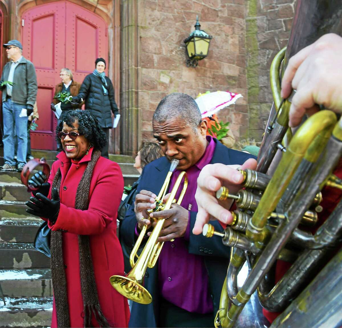 """Aleta Straton of New Haven play the tambourine and sings, left, as The Episcopal Church of St. Paul & St. James in New Haven holds a Palm Sunday New Orleans """"second line"""" jazz style procession, its annual Parasols & Palms Parade, Sunday from the church on Chapel Street, around Olive Street to Wooster Street and back to the church."""