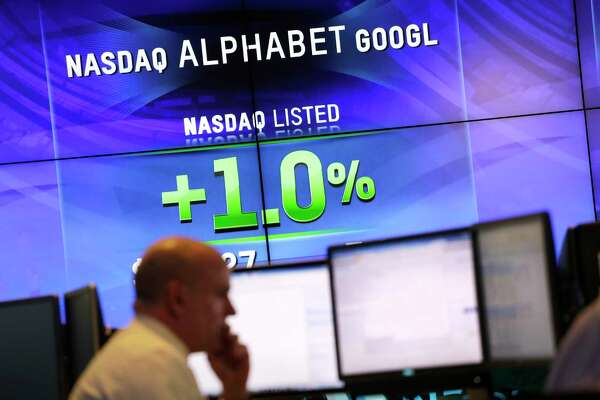 FILE - In this Monday, Feb. 1, 2016, file photo, electronic screens post the price of Alphabet stock at the Nasdaq MarketSite in New York. Google parent Alphabet is taking a $2.7 billion write-down to cover a large fine EU antitrust enforcers assessed in June 2017. While the search giant can shrug off the cost, uncertainty lingers over its ability to operate freely on the continent going forward. (AP Photo/Mark Lennihan, File)