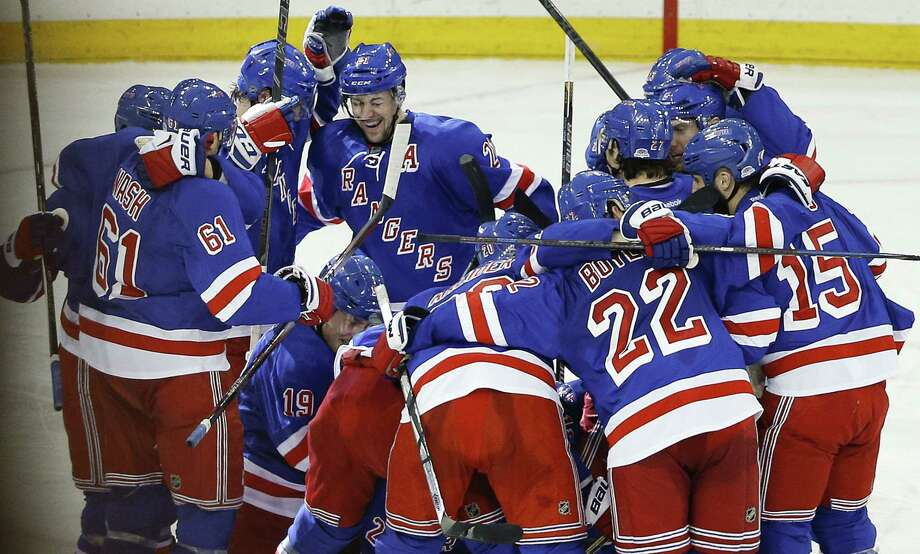 The Rangers celebrate after beating the Pittsburgh Penguins 2-1 in overtime of Game 5 in the first round of the Stanley Cup playoffs on Friday in New York. Photo: Julie Jacobson — The Associated Press   / AP