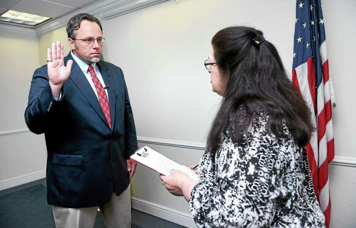 (Arnold Gold-New Haven Register) Hamden Mayor Curt Leng (left) is sworn into office by Town Clerk Vera Morrison at the Hamden Government Center on 5/29/2015.