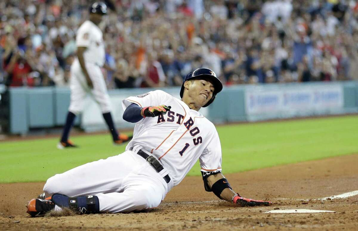 Houston Astros rookie Carlos Correa slides across home plate during the fourth inning of Sunday's game in Houston.