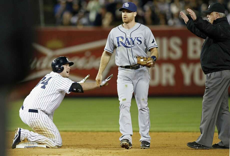 The Yankees' Brian McCann, left, gestures to second base umpire Jim Joyce that he is safe after hitting a fifth-inning, two-run double against the Tampa Bay Rays. Photo: Kathy Willens — The Associated Press   / AP