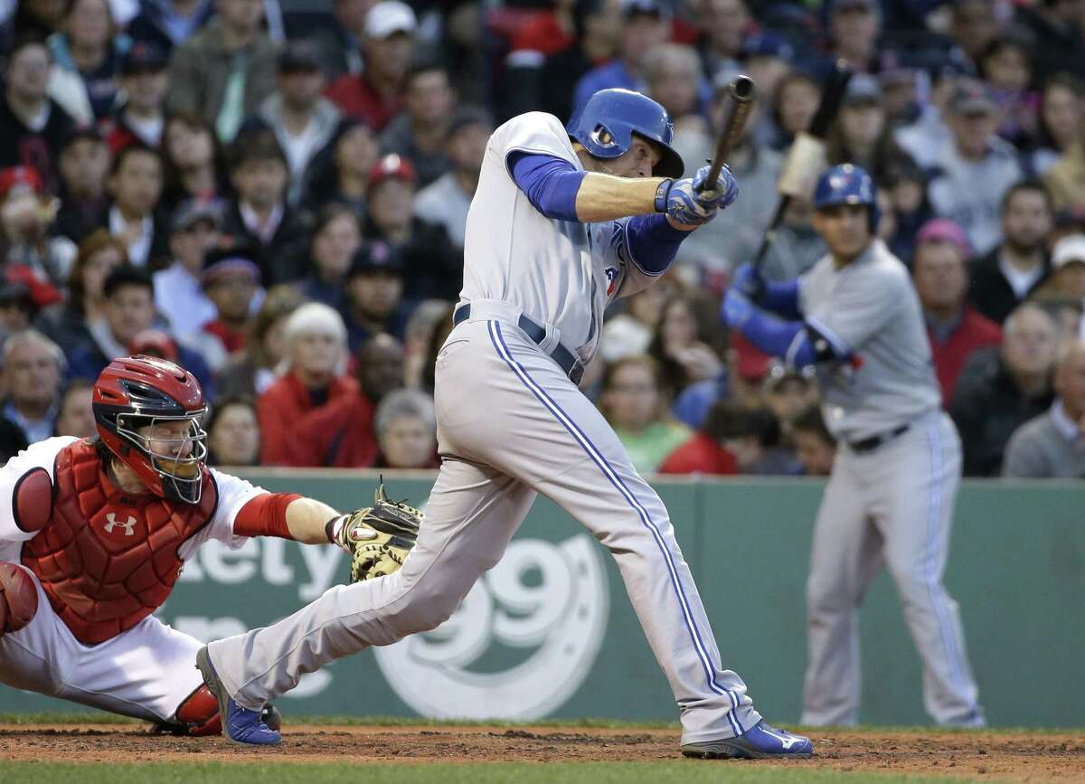 The Blue Jays' Michael Saunders hits an RBI single as Red Sox catcher Ryan Hanigan looks on in Tuesday's game.