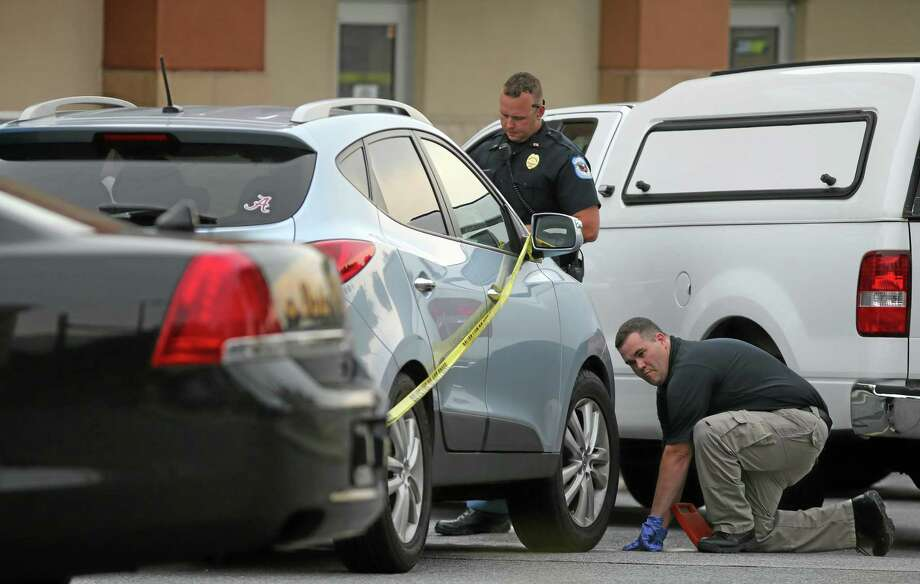 In this Wednesday, June 18, 2014 file photo Cobb County police investigate an SUV where a toddler died near Marietta, Ga., when the father forgot to drop his child off at day care and went to work. (AP Photo/Atlanta Journal Constitution, Ben Gray, file) Photo: AP / Atlanta Journal-Constitution